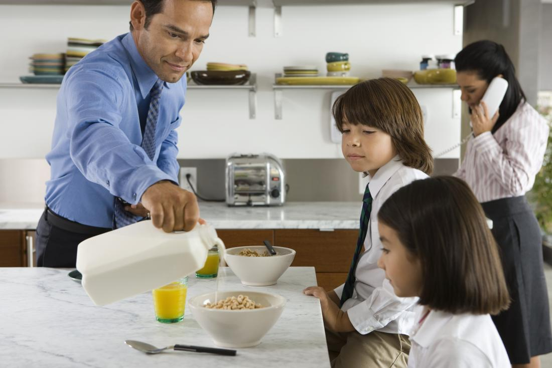 father pouring milk on to his childrens cereal