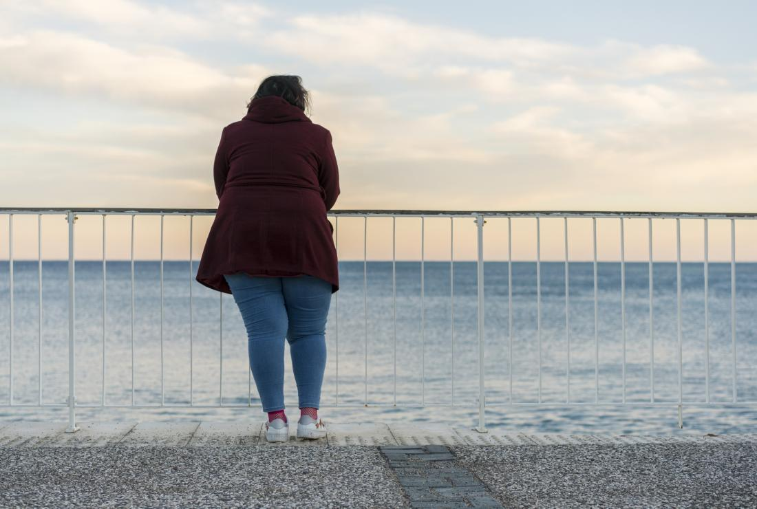 obese woman looking at the sea