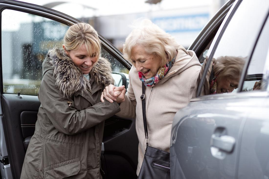 woman helping mother getting out of the car