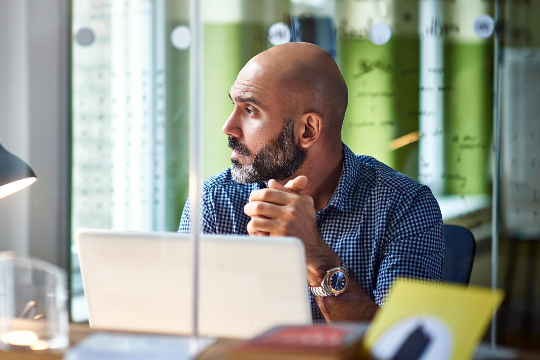 a man in an office who is distracted because of ruminating thoughts