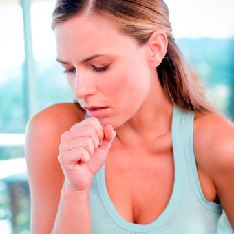 A woman with a sore throat coughs and covers her mouth to avoid spreading infection.