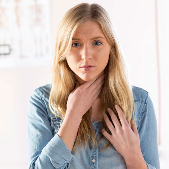 A woman with laryngitis holds her sore throat.