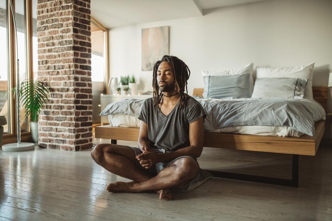 person meditating on bedroom floor