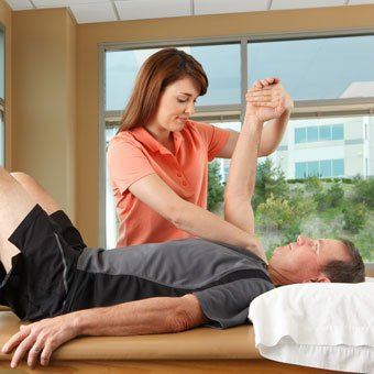 A physical therapist performs shoulder stretching exercises on a patient.