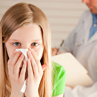 A girl blowing her nose at a doctor's office.