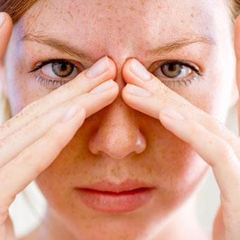 A woman in pain with a sinus headache.