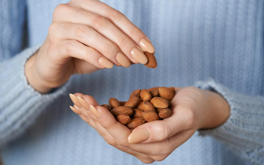 a dosage of nuts with nCoq10 in a womans hand