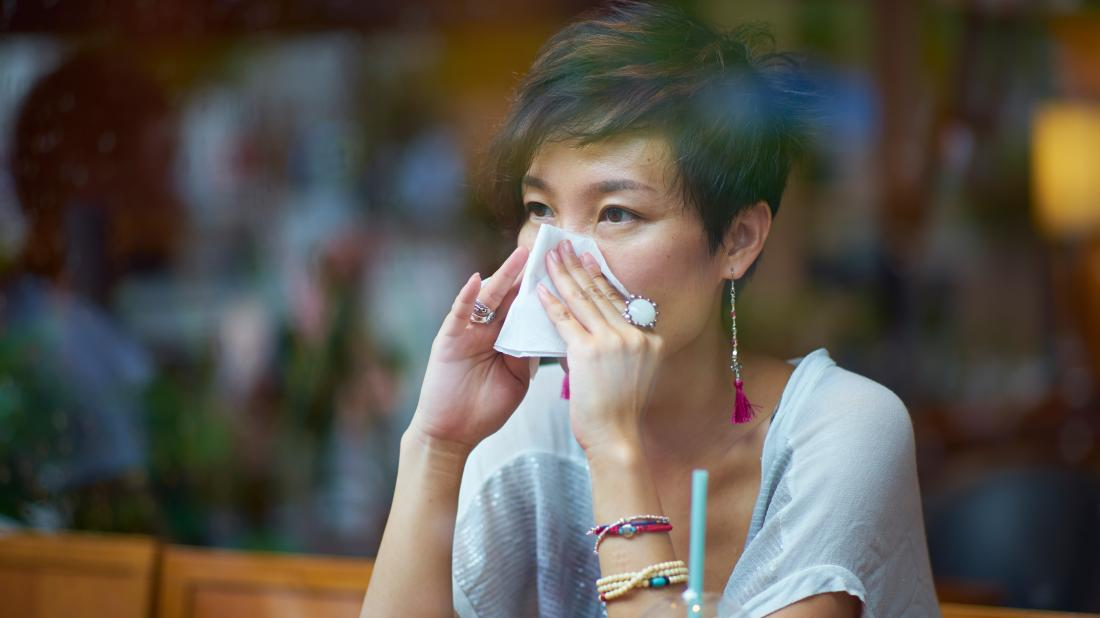 a woman blowing her nose because she has ethmoid sinusitis