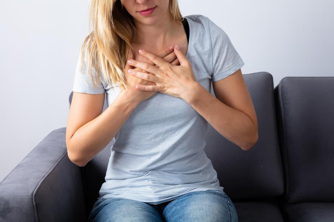Woman holding her chest due to excessive burping